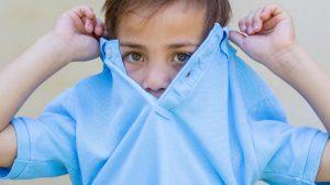 ילד מרים את החולצה שלו